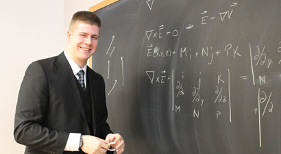 Photo of Cole Martin in front of a blackboard filled with physics equations