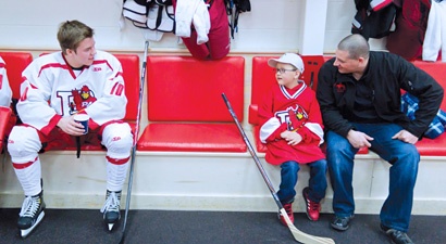 Photo of a men's hockey team member talking to Matthew Wood and his father in the locker room