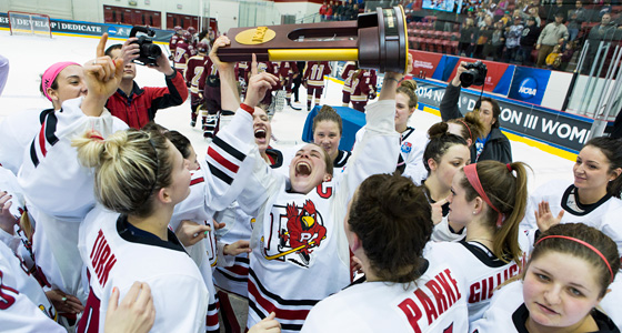 The women's hockey team gathers around as a member exuberantly lifts the trophy over her head